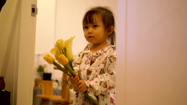 Thai baby girl carry flower while playing with her brother at the bedroom before go bed