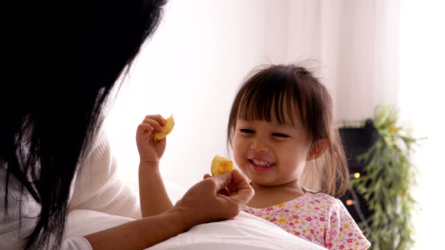thai baby girl is eating chip with her mother at the bedroom with positive emotion - crisps stock videos & royalty-free footage