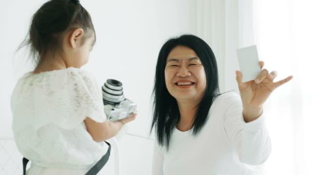 タイの女の子は彼女の週末の活動に趣味とリラクゼーションのための彼女の母の写真を撮るを楽しんでいます。 - photographing点の映像素材/bロール