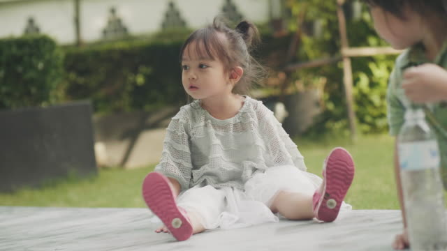 thai baby girl is looking to her parent beside her brother at the garden - shy stock videos & royalty-free footage
