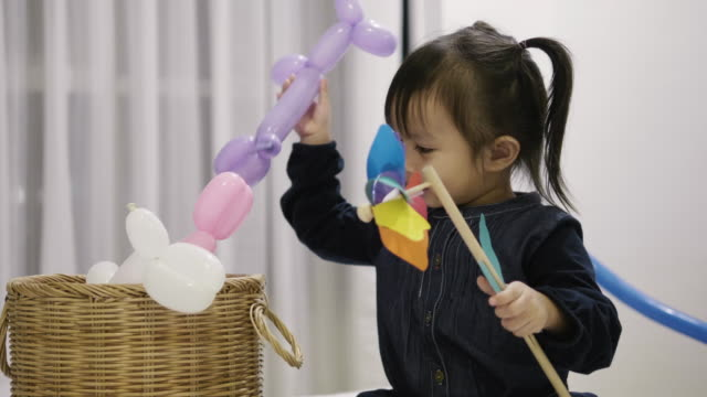 Thai baby girl is playing a shape of balloon like a dog with positive emotion and relaxation -diy of balloon shape