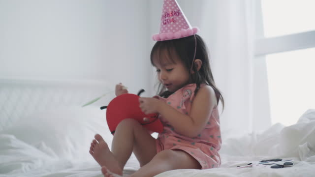 Thai baby girl is playing toy while lying down to her bedroom