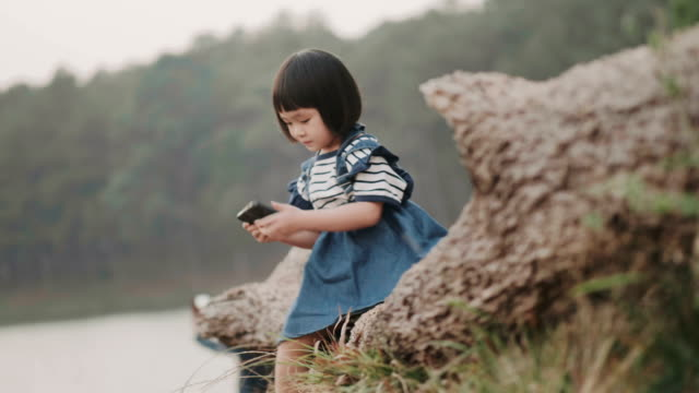 Thai baby girl is using smart phone for relax while she is sitting on lump of wood seat at the pond-travel while using smart phone with technology concept