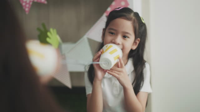 タイ、女児は音声コールを作るためのカップを使用して - リサイクル素材点の映像素材/bロール