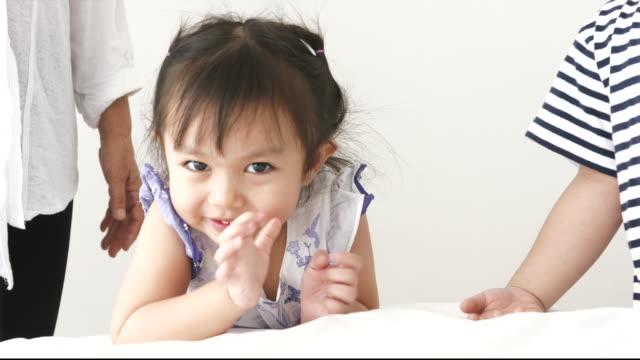 stockvideo's en b-roll-footage met thai baby meisje terwijl het proberen om te uiten van kussen en zeggen bye met video film met haar broer en moeder - zwaaien gebaren