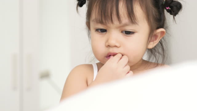 Thai baby is eating some popcorn while watching cartoon with digital tablet at the bedroom