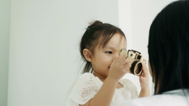 タイの赤ちゃん木のおもちゃカメラを使用して写真趣味のための彼女の白い部屋の彼女の母親 - photographing点の映像素材/bロール
