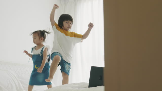 thai boy and girl is dancing while watching computer laptop at the bedroom - small stock videos & royalty-free footage