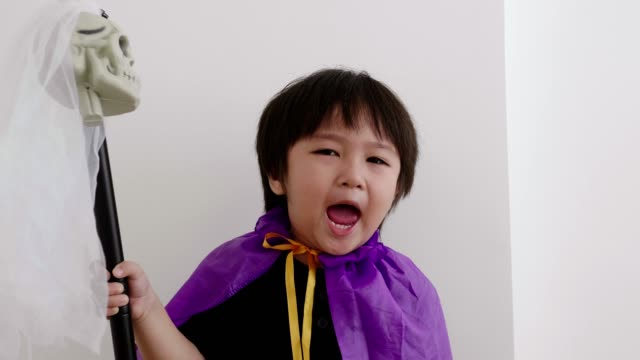thai boy with halloween costume while acting and playing with halloween skull and spear toy at home-halloween concept - human skeleton stock videos and b-roll footage