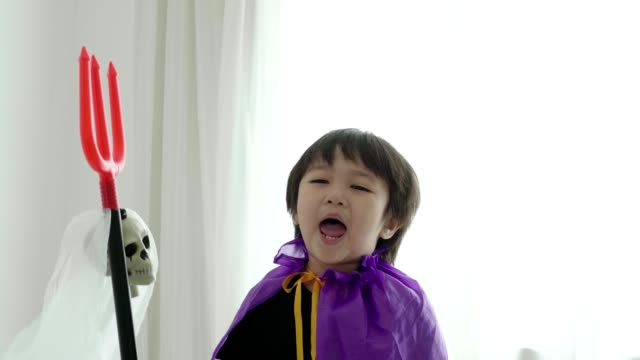thai boy with halloween costume while acting and playing with halloween skull and spear toy at home-halloween concept - halloween stock videos & royalty-free footage