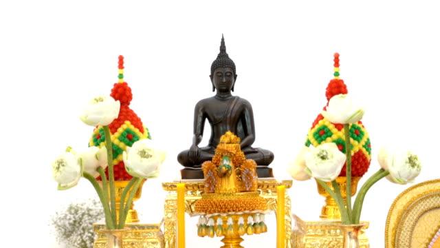 vídeos y material grabado en eventos de stock de estatua de buda tailandés 4k con vela sobre fondo blanco - posa del loto