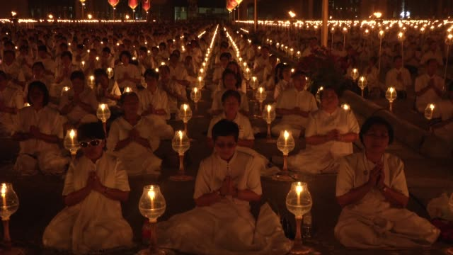 Thai Buddhists and devotees take part in a candle lighting ceremony at Wat Phra Dhammakaya in Bangkok Thailand During the Buddhist holiday of Makha...