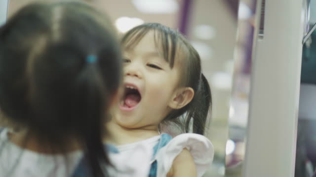 thai child girl making her face humor with reflection of the mirror - baby girls stock videos & royalty-free footage