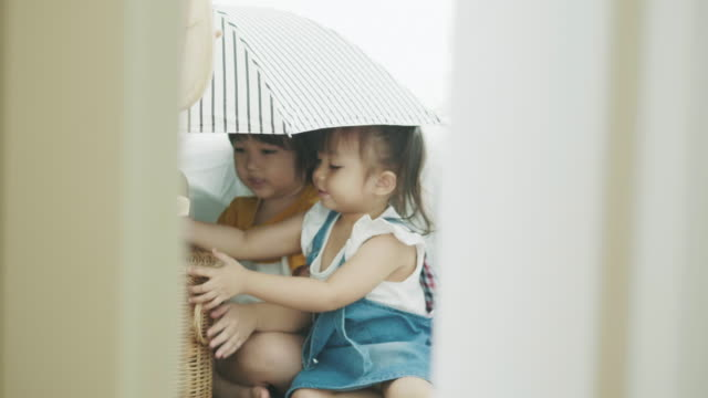 thai children is hiding in the umbrella and playing leisure game the the bedroom - peekaboo game stock videos & royalty-free footage