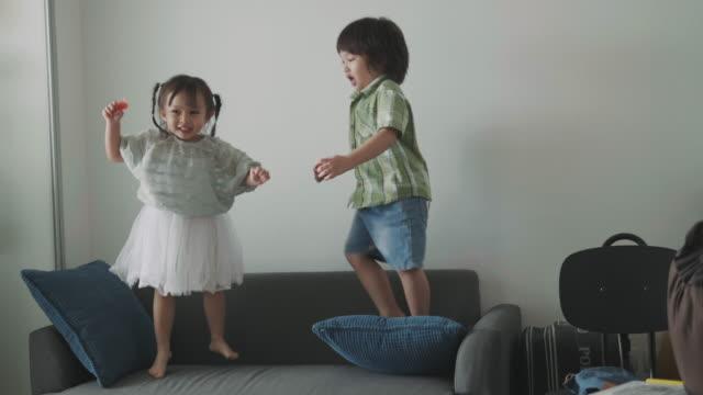 thai niedlichen baby mädchen und kleinkind jungen tanzen und spielen auf dem sofa im wohnzimmer - stock video - applaudieren stock-videos und b-roll-filmmaterial