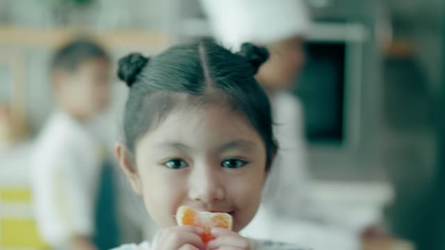 thai cute baby girl carrying orange while looking at camera with positive emotion - fruit stock videos & royalty-free footage
