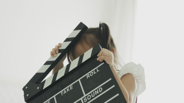 thai cute baby girl is carrying clapper board in her white room - film director stock videos & royalty-free footage