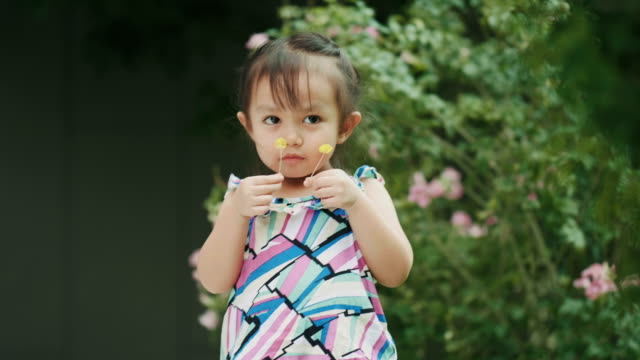 Thai cute baby girl is carrying flower while smell of it at the garden