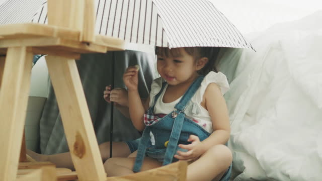 thai cute baby girl is eating candy while dancing beside her brother under umbrella - rhythm stock videos and b-roll footage