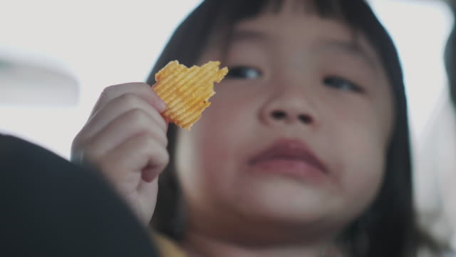 thai cute baby girl is eating potato chip in the car while traveling on weekend with her family - snack stock videos & royalty-free footage