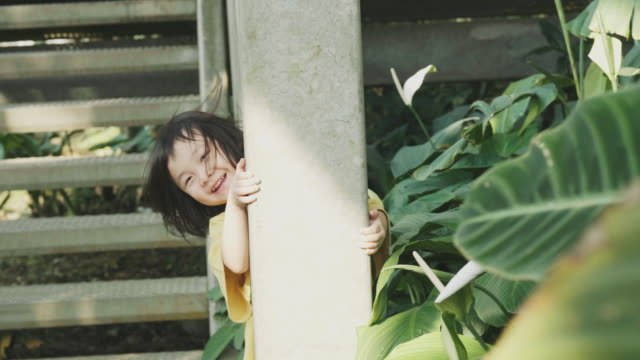 Thai cute baby girl is playing hide and seek game beside column and the tree at public park