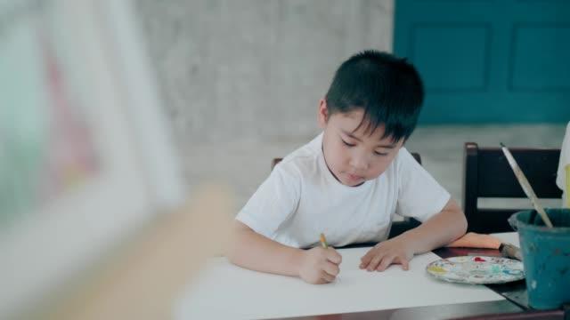 教室でアートの主題でタイのかわいい男の子の描画とスケッチのアイデア - 鉛筆点の映像素材/bロール