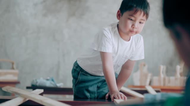 thai cute boy supporting his brother to carry wood while working furniture design class - 10 11 years stock videos & royalty-free footage