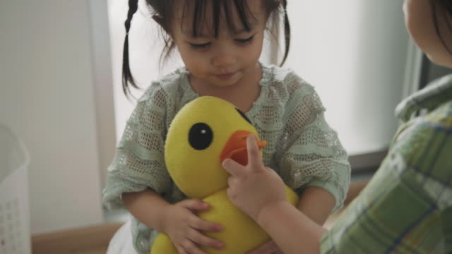 thai cute child is embracing her ducky doll beside her brother - doll stock videos & royalty-free footage