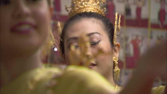 thai dancers gracefully perform in gold lame robes and gold jewelry. - thai culture stock videos & royalty-free footage