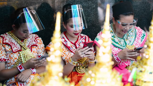 thai dancers wearing protective face shields using their phones in their traditional dance outfit at erawan shrine - エラワン聖堂点の映像素材/bロール