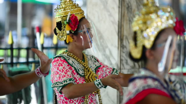 thai dancers wearing protective face shields with their traditional headdress and decorate outfit while performing at erawan shrine - エラワン聖堂点の映像素材/bロール