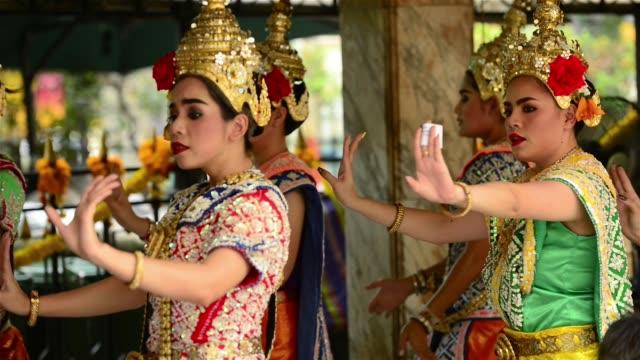thai dancers wearing traditional headdress and decorate outfit performing at erawan shrine - エラワン聖堂点の映像素材/bロール