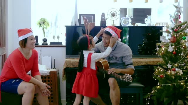 thai daughter is helping her father to wear santa hat before having new year and christmas party at home - santa hat stock videos & royalty-free footage