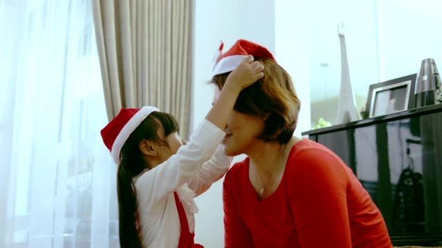 thai daughter support her mother to wear santa hat with her christmas party at home - santa hat stock videos & royalty-free footage