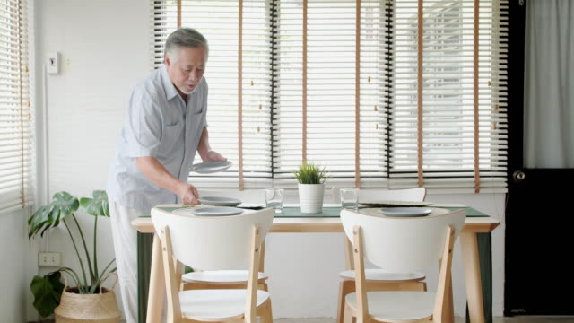 thai families at home:senior man setting table dining room preparing plates.senior preparing table for a dinner party - setting the table stock videos & royalty-free footage