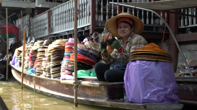 thai female traders wearing traditional mo hom apparel use sampans (small wooden boats) to sell their wares at damnoen saduak floating market - floating market stock videos & royalty-free footage