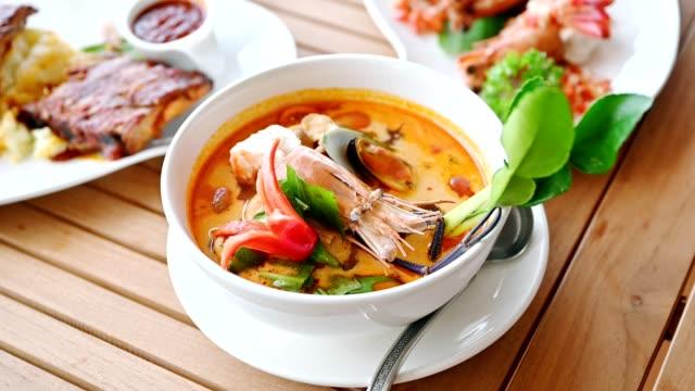 タイ料理、トム・ヤムカンフー、木のテーブルの上のエビ、シェル、ハーブとスパイシーなスープ - ベルガモット点の映像素材/bロール