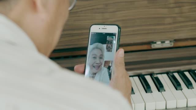 vídeos y material grabado en eventos de stock de abuelo tailandés hablando con la abuela mientras usa el teléfono inteligente en su casa con amor y lo extraña - recordatorio