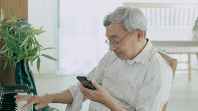vídeos de stock e filmes b-roll de thai grandfather talking to her wife while using smart phone in her house with love and missing him - músico