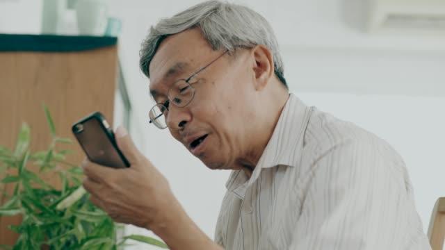 タイの祖父は、愛と彼を失って彼女の家でスマートフォンを使用しながら、彼女の妻に話す - 電話を使う点の映像素材/bロール