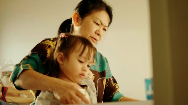 thai grandmother is teaching homework to her niece - art and craft stock videos & royalty-free footage