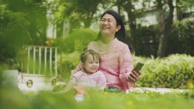 thai grandmother with her niece resting at the garden by using smart phone for taking picture and watching,dancing with her positive emotion - 50 59 years stock videos & royalty-free footage