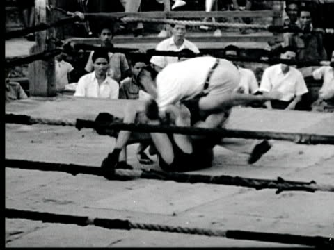 1948 B/W MONTAGE Thai kick boxing match in ring with referee and audience in bleachers / Bango, Thailand