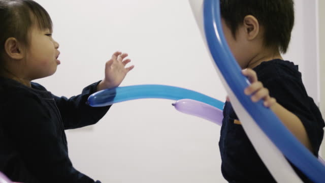 Thai little boy and girl quarrel while playing of balloon -diy of balloon shape