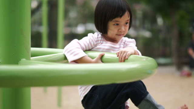 Thai little girl is climbing and playing at the playground -video stock