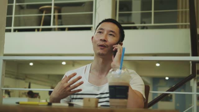 タイの男はカフェでスマート フォンを使用している間彼の仕事を話し合う - タイ人点の映像素材/bロール