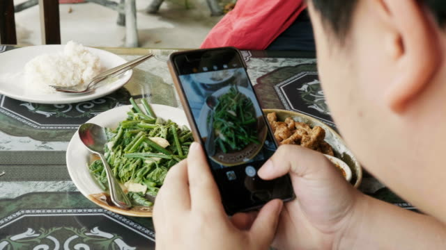 thai man is taking picture of food by using smart phone at the restaurant before having lunch - photograph stock videos & royalty-free footage