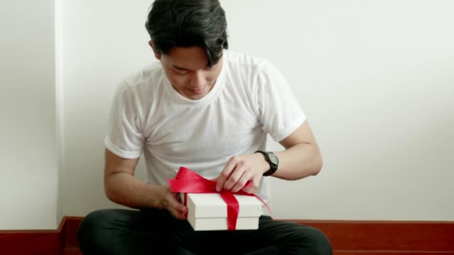 thai man trying to make gift box for surprise to girlfriend for valentine and birthday celebration - tied bow stock videos & royalty-free footage