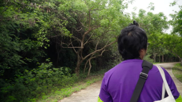 Thai man with hair of topknot walking in denuded forest