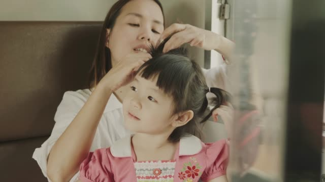 Thai mother is braiding pigtails to her daughter while sitting on the train
